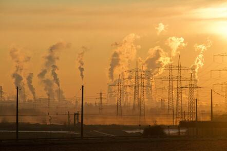 Sunset over a landscape of pylons and industrial towers with plumes of smoke.