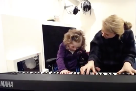 A screen shot from the video Mary and Antonio showing a young girl is playing an electric keyboard with a female music therapist