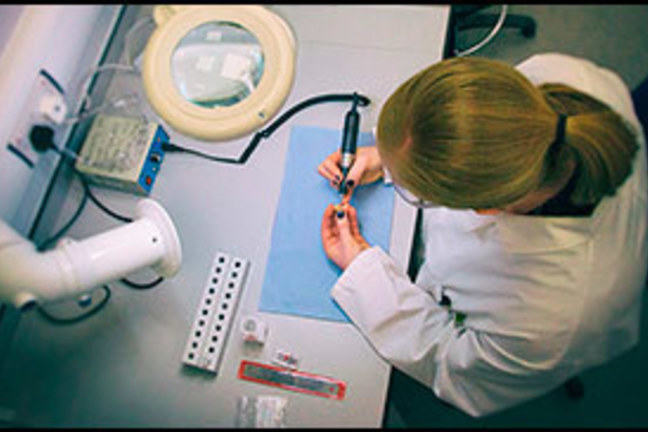 A women works at a desk to prepare a sample for isotope analysis. The view is from above and is in a lab.