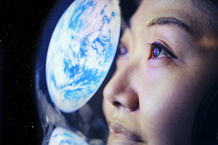 Photo of earth reflected in astronaut's helmet as they look out into space