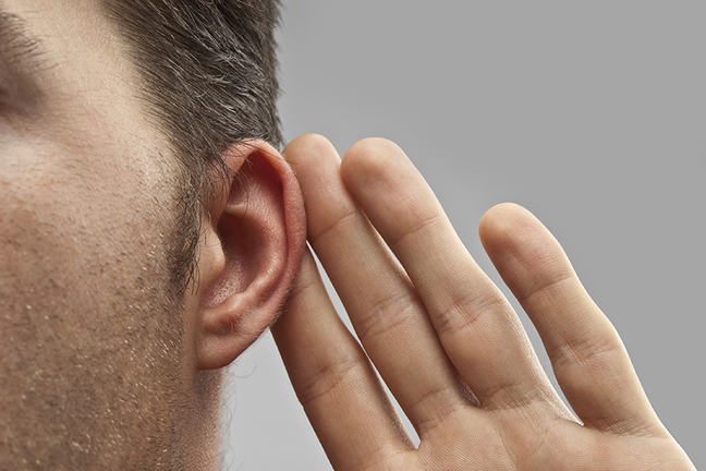 A close up of a man's ear. He holds his hand up to it to indicate that he's listening.