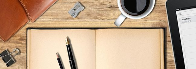 The course image for Start Writing Fiction. A pen and pencil sit on an open notebook with a coffee and an iPad close at hand, ready to start writing.
