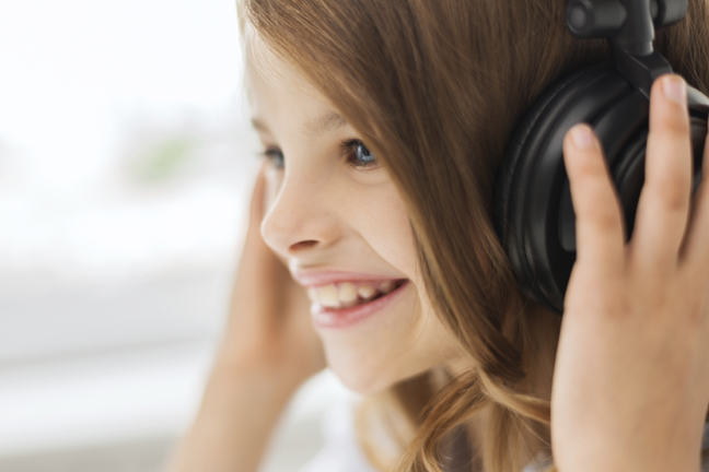 Close up image of girl with headphones on listening to sounds