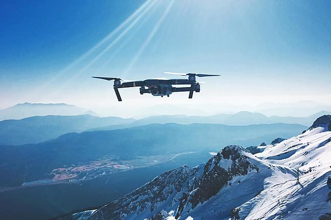 An image of a drone flying about a mountainous landscape.