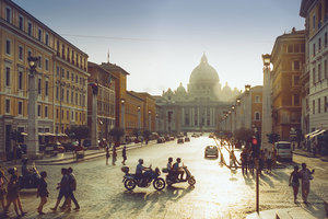 Photograph of a busy street in Rome with St. Peter's Basilica in the distance