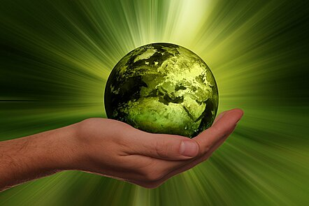 Picture of a greened out Earth in the palm of a hand