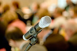 An image of a microphone in front of an audience
