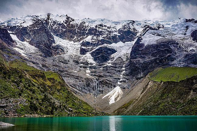 An image showing a series of glaciers and a turquoise proglacial lake in the foreground.