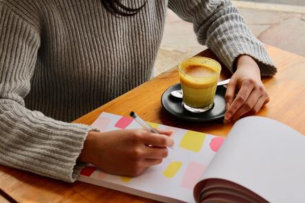 A person making notes on a notepad with a cup of milky coffee