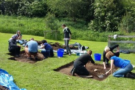 people excavating several grave sites in a field.
