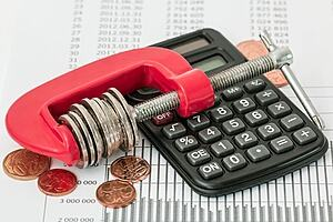 Photo of some coins in a vice with a calculator in the foreground
