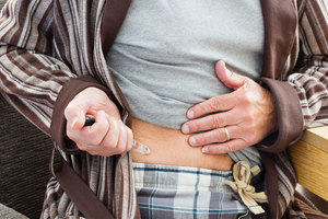 Senior man injecting insulin into his stomach.