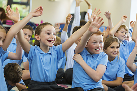 Children with hands up in the classroom