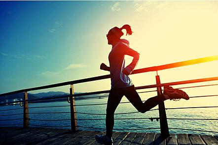 A woman running along a boardwalk in the sun.