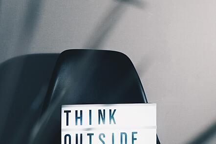 Think outside the box sign on a black chair