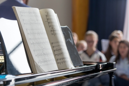 Sheet music is sitting on a piano and a choir group is in soft focus in the background.