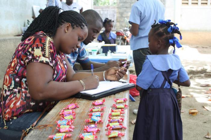 This image depicts a Haitian man and woman sat at a table. The woman is filling out a paper form with a pen. In front of the table, standing, is a small girl wearing a blue school uniform. There are many individually wrapped sweets on the table.