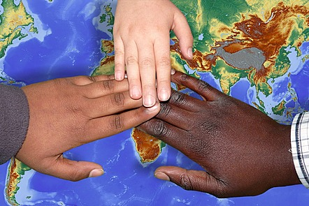 Three hands touching over a map