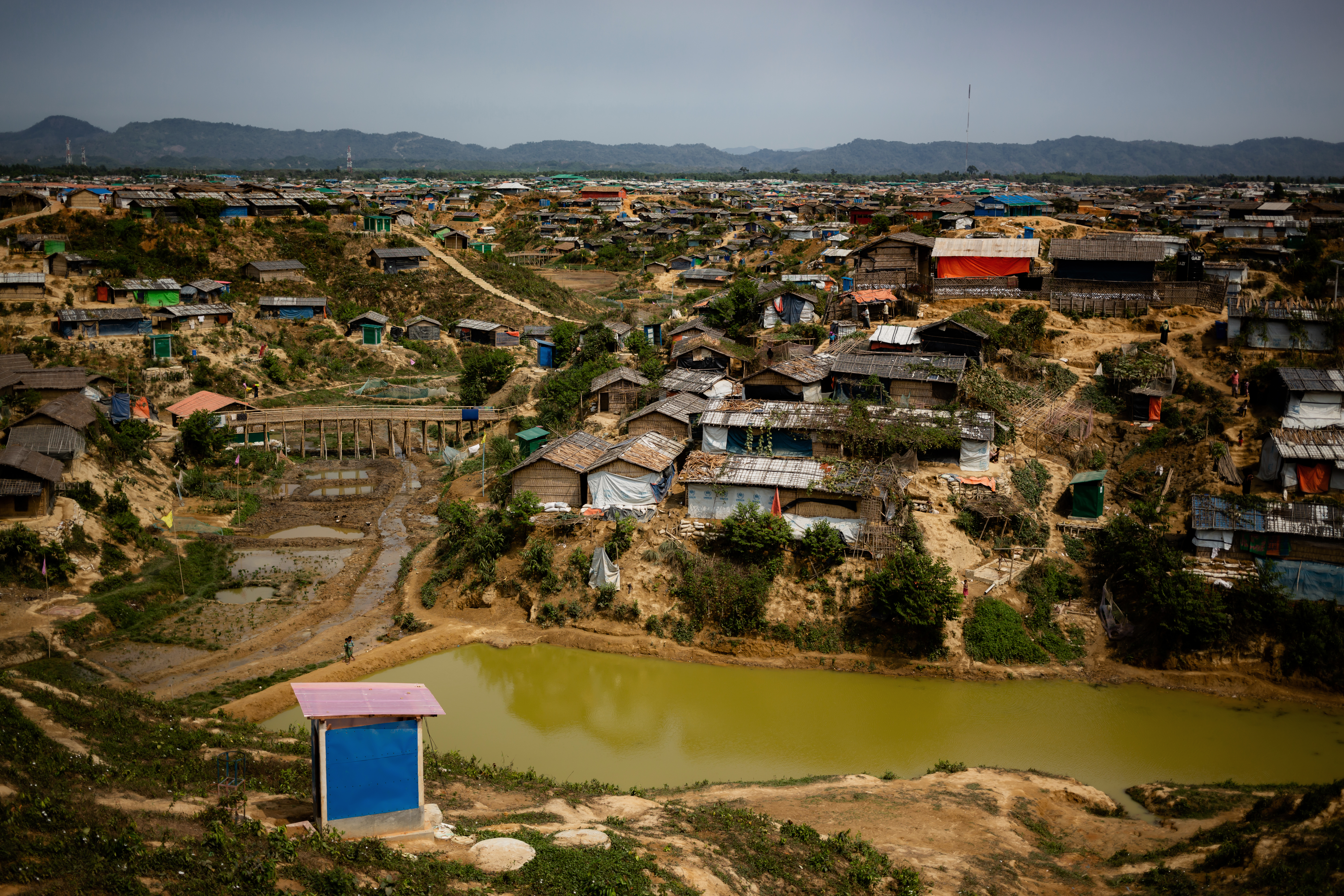 The Kutapalong Rohingya refugee camp is composed of hundreds of houses built on a muddy, piece of land with a river flowing in front of it. A shed stands on the opposite side of the river. This is home to more than one million displaced people.