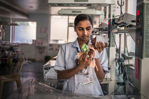 Nurse holding a very preterm baby in a neonatal intensive care unit, India
