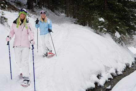 Two women walks in the snow with snowshoes