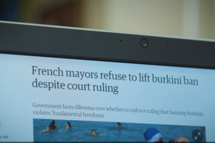The top half of a computer screen, showing the news article 'French mayors refuse to lift burkini ban despite court ruling'