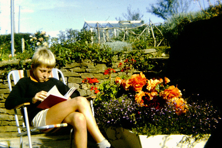 Photgraph of a boy reading a book outside.