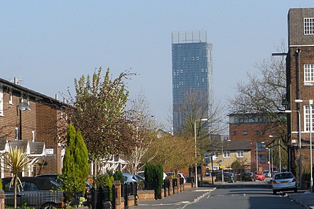 A photograph of a street in modern day Moss Side with the Hilton Tower in the background.