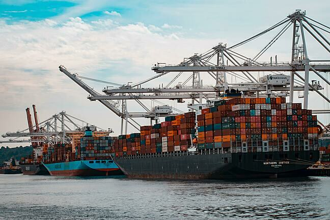 Image of 3 cargo ships in Seattle USA with 8 layers of containers on each ship and cranes over each ship. Closest ship has Northern Justice Madeira written on the ship