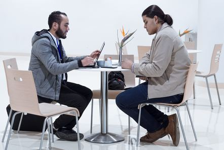 Two men sat at tables having a meeting