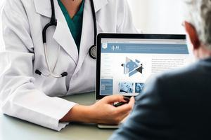 doctor showing laptop image on a person in black top ©Photo by rawpixel on Unsplash