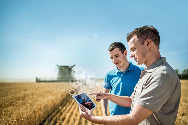 Two men stand in a field looking at a tablet