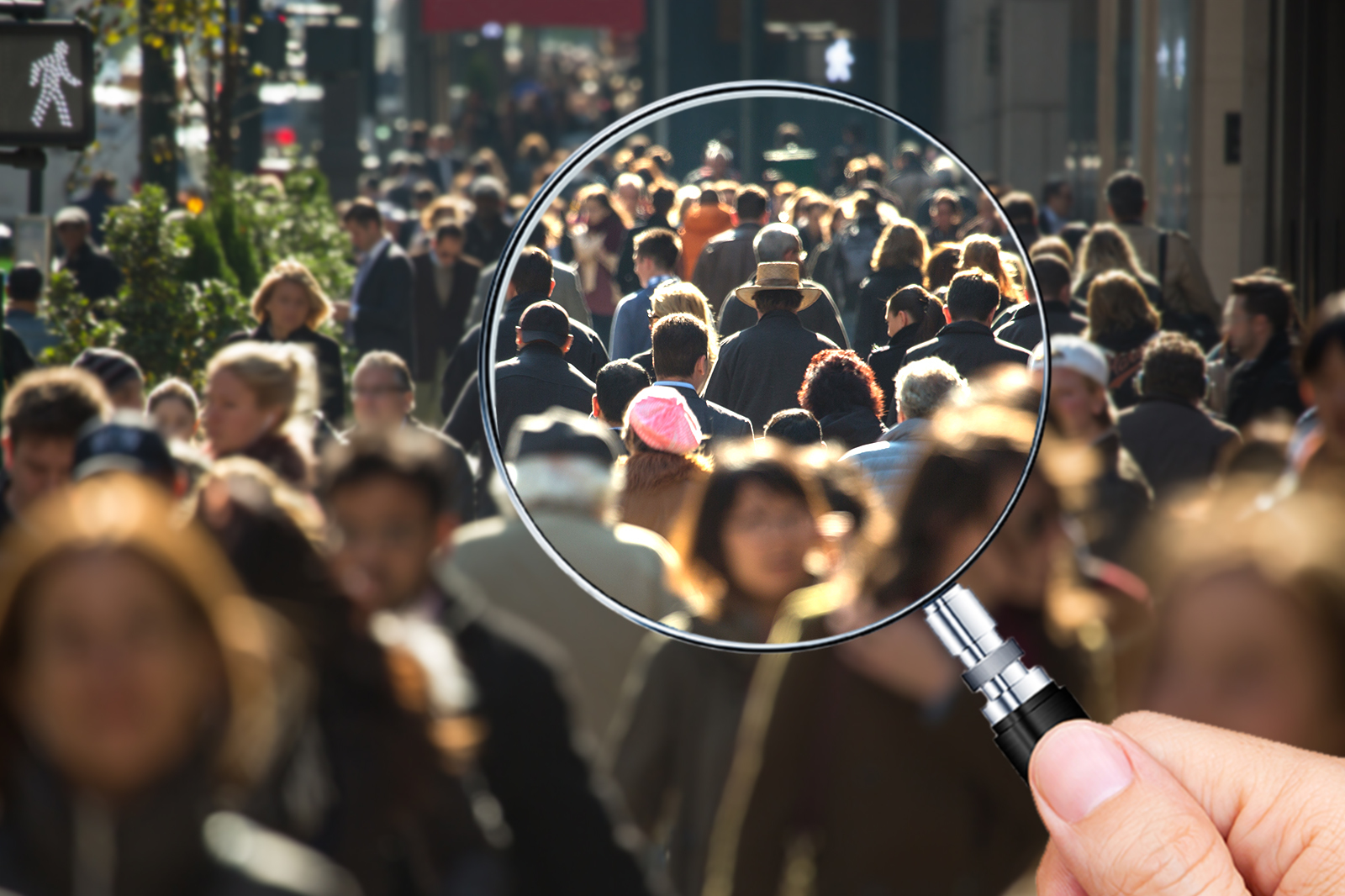 a handheld magnifying glass held over an image of people