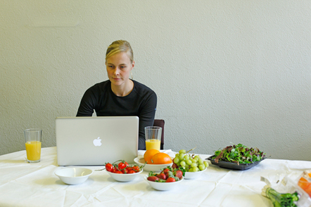 A woman working on a laptop, surrounded by bowls of fruit and vegetables