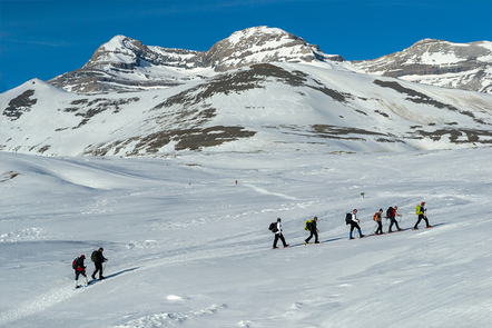 A group of people on an expedition heading up a snowy mountain.