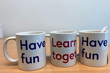 Threde mugs in a row. On the sides of two is printed 'Have fun'. The other says 'Learn together'