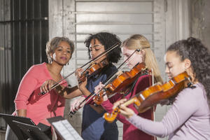 Image showing female violin teacher instructing three young students