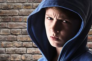 Boy in a hooded shirt scowling in front of a brick wall.