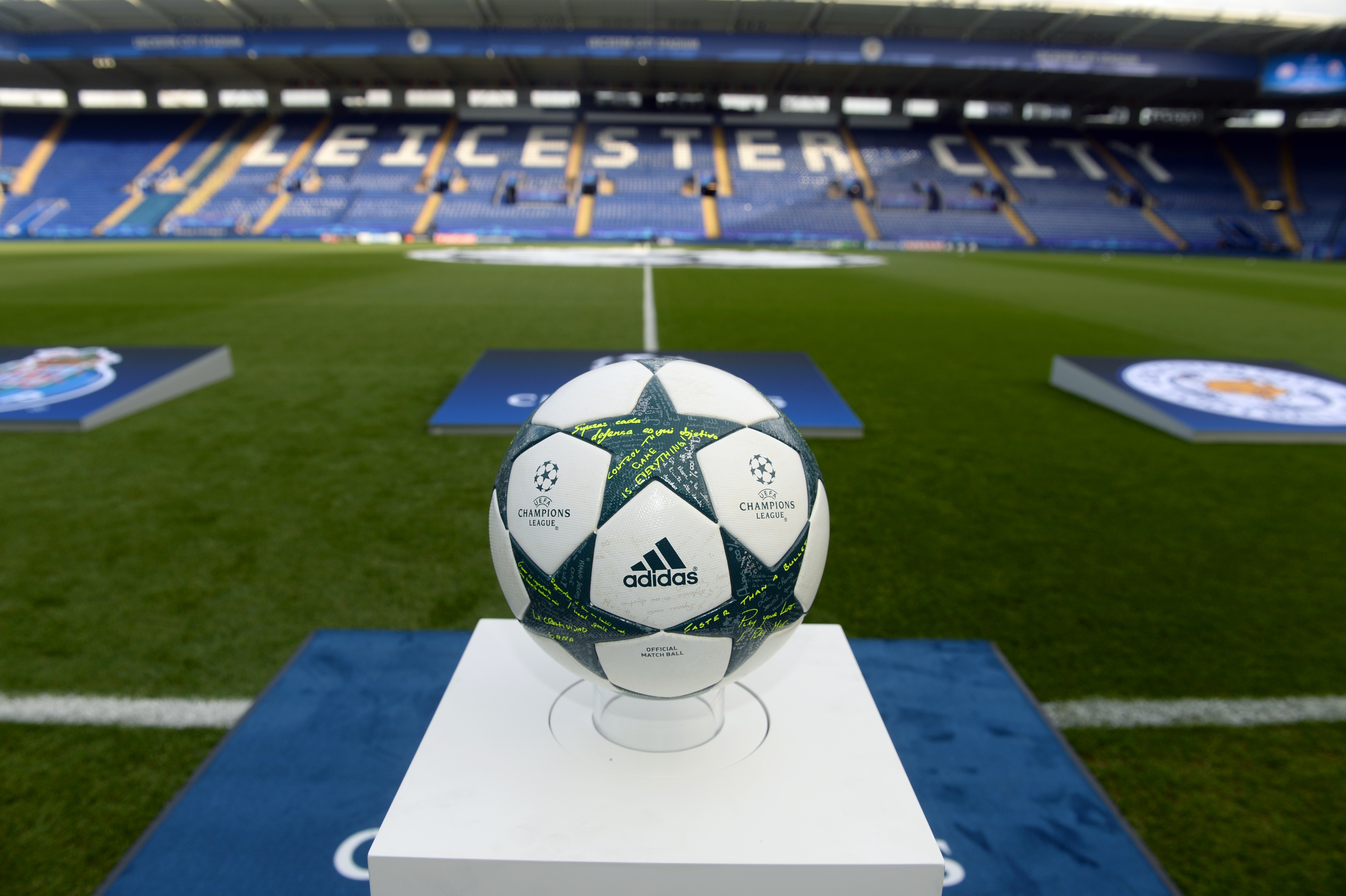 A Champions League football resting on a pedastal within an empty stadium.