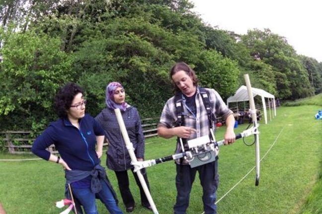 Two people being instructed by another about how to use a geophysical technique