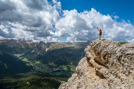 A dramatic view from a mountain top with green valley below and further mountains in the distance. A person stands on an outcrop in the foreground and raises both arms towards the blue sky.