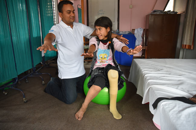 A rehabilitation session with Reema Puri (13) and Ashok Paudel, a physiotherapist at National Disabled Fund Rehabilitation Centre, Nepal