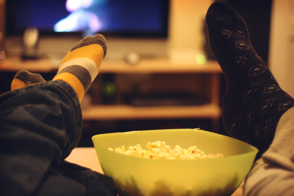 Image of children's legs resting on a lounge next to a bowl of popcorm in front of a television