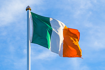 A painting of an Irish flag waving in the wind against a cloudy blue sky.