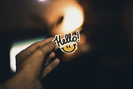 A hand holds a sticker with a smiley face on it reading 'Hello'.