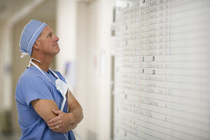 Doctor looking at schedule whiteboard in hospital
