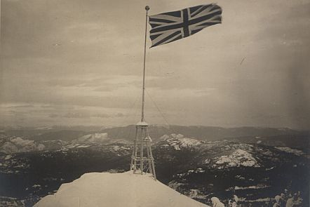 Union Jack standing on top of an icy mountain in a bleak landscape