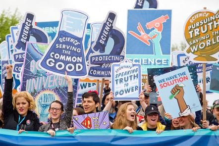 Crowd holding signs promoting science with slogans like 'Science : Serving the Common Good' and 'Science: Pursuing the Truth, Saving the World'