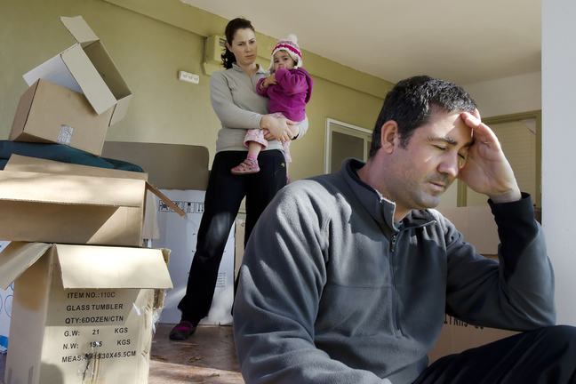 Young parents and their daughter with cardboard boxes.