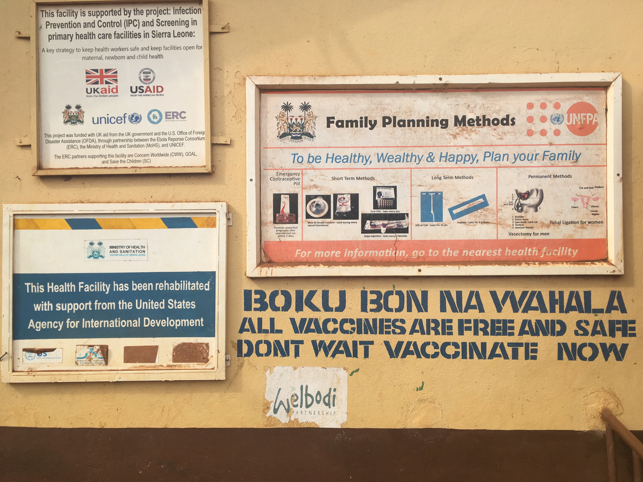 The wall of a health centre with signs, including one advising on available vaccinations
